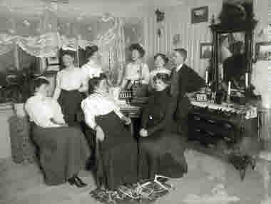 Interiörbild av grupp i hemmiljö år 1915.